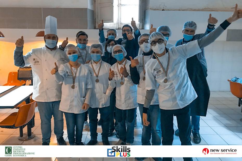 SkillsPlus Gara di abilità per persone con disabilità - undici ragazzi del cirpe, tutti vestiti con la divisa da cuoco, con il pollice in su in posa insieme al tutor william di noto sull sfondo